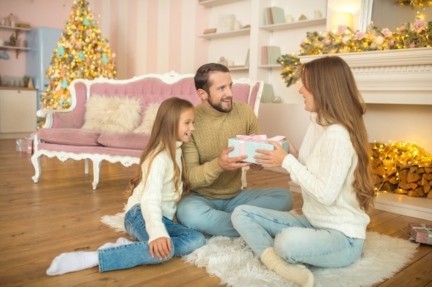 興奮しました。床に座ってクリスマスプレゼントを交換する若い家族
