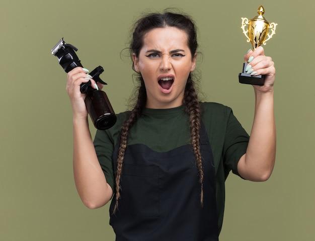 Возбужденная молодая женщина-парикмахер в униформе держит кубок победителя с машинкой для стрижки волос, изолированной на оливково-зеленой стене