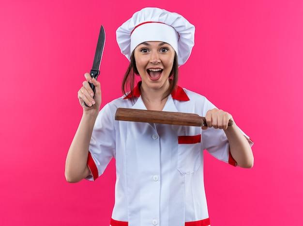 분홍 벽에 도마가 달린 칼을 들고 요리사 유니폼을 입은 흥분한 젊은 여성 요리사