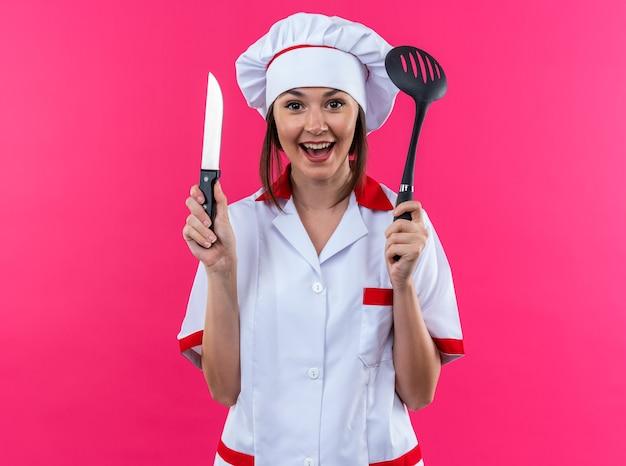 ピンクの背景で隔離のへらとナイフを保持しているシェフの制服を着て興奮した若い女性料理人