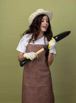 ガーデニングの帽子と手袋を身に着けている制服を着た興奮した若い女性の庭師は、オリーブグリーンの壁に隔離されたスペードを保持し、見ています