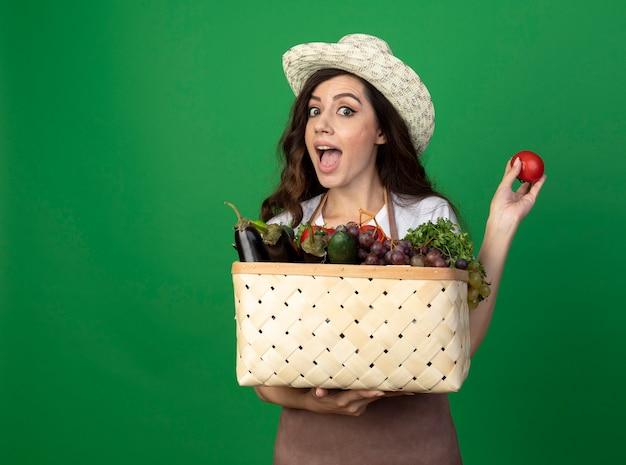 ガーデニング帽子を身に着けている制服を着た興奮した若い女性の庭師は、緑の壁に隔離された野菜のバスケットとトマトを保持します