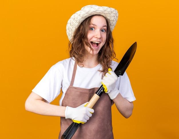 주황색 벽에 격리된 삽을 들고 장갑을 낀 원예용 모자를 쓴 흥분한 젊은 여성 정원사