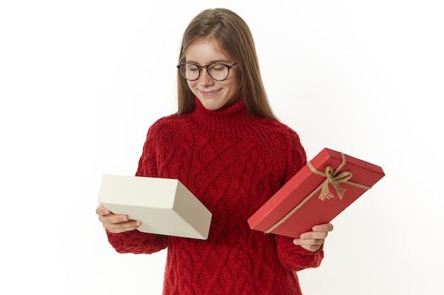 그녀의 생일에 예기치 않은 깜짝 선물을 즐기는 안경에 흥분된 젊은 여성, 웃고, 상자를 들고