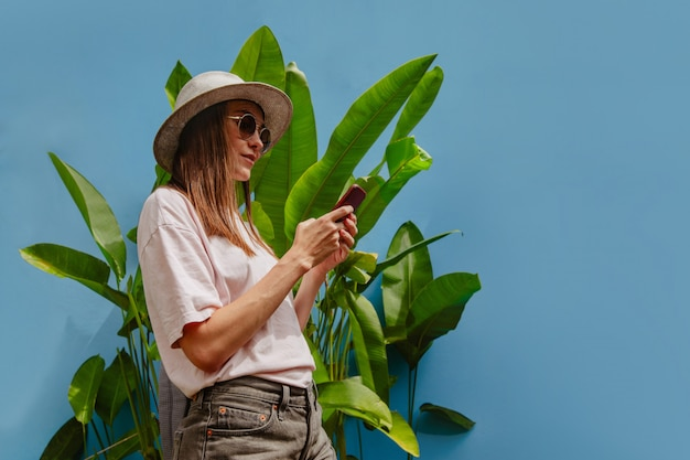 Excited young female on vacation uses smartphone