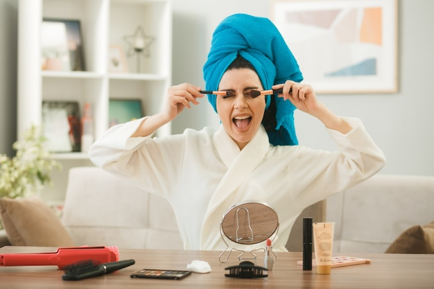 リビングルームで化粧ツールとテーブルに座って化粧ブラシでアイシャドウを適用する興奮した若い女の子