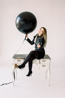 Excited young girl in black dress celebrating holding black balloon and sitting on white vintage table isolated on white background. international women's day, happy new year, birthday party concept