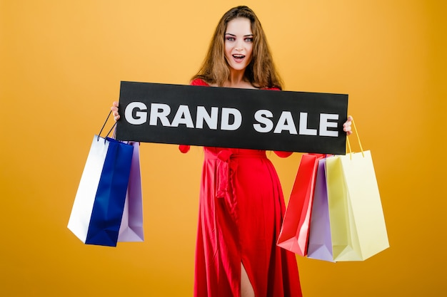 Excited young girl has grand sale sign with colorful shopping bags isolated over yellow