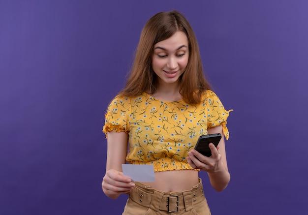 Ragazza eccitata che tiene il telefono cellulare e la carta e guardando il telefono cellulare sullo spazio viola isolato con lo spazio della copia