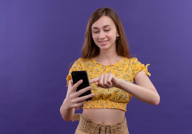 Ragazza emozionante che tiene il telefono cellulare e che mette il dito su di esso sullo spazio viola isolato con lo spazio della copia