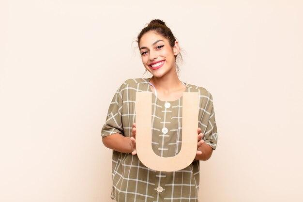 単語または文を形成するアルファベットのuの文字を保持している興奮している若い女の子