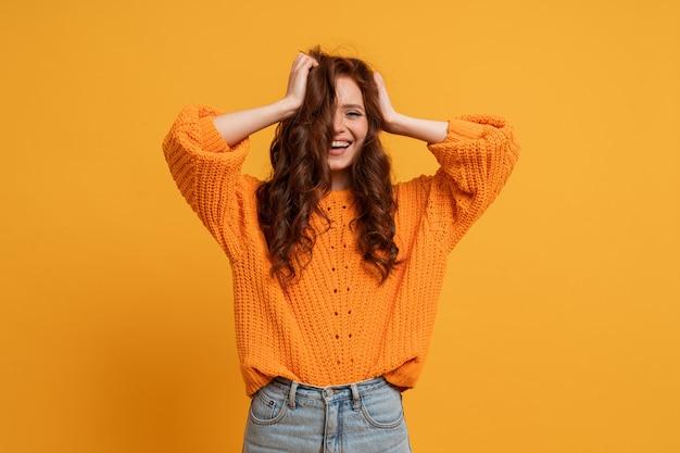 노란 스웨터를 입은 흥분한 어린 소녀가 노란 벽에 격리된 펄럭이는 머리카락으로 점프하는 스튜디오에서 장난을 치고 있습니다.