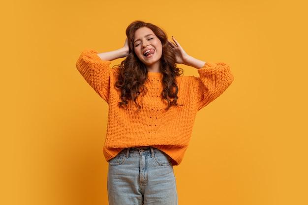 노란 스웨터를 입은 흥분한 어린 소녀가 노란 벽에 물결 모양의 머리를 하고 스튜디오에서 포즈를 취하고 있다