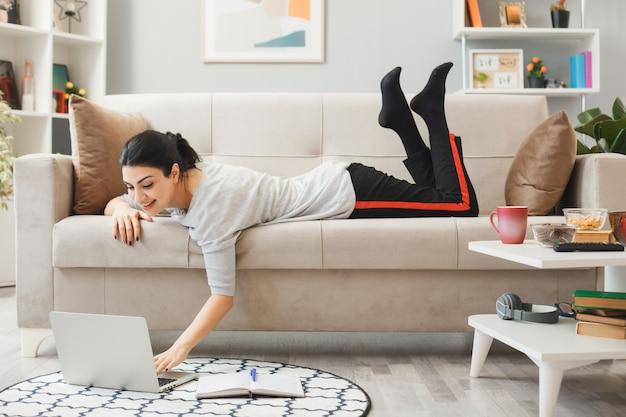 소파에 누워 흥분된 어린 소녀는 거실에서 노트북을 사용했습니다.