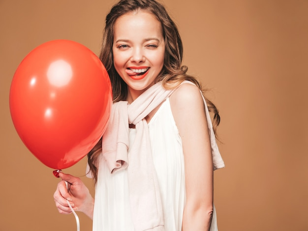 유행 여름 흰 드레스에 포즈 흥분된 어린 소녀. 빨간 풍선 포즈와 여자 모델. 그녀의 혀를 보여주는 파티를위한 준비