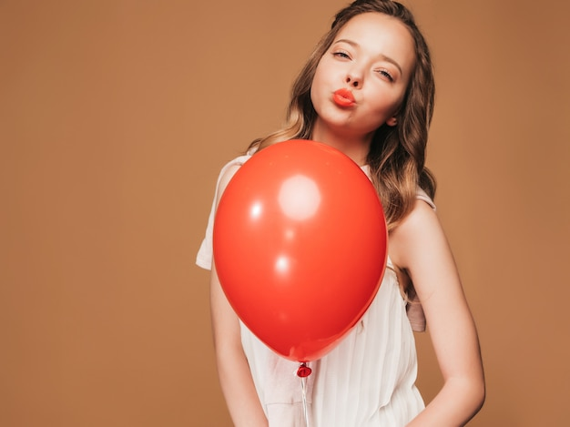Excited young girl posing in trendy summer white dress. woman model with red balloon posing. ready for party and giving kiss