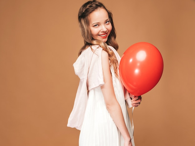 Excited young girl posing in trendy summer white dress. woman model with red balloon posing. ready for party