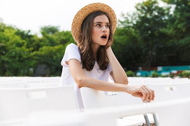 여름에 야외 도시 공원에 앉아 흥분된 어린 소녀