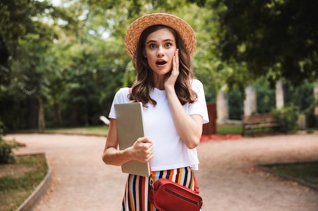 Возбужденная молодая девушка сидит с портативным компьютером в парке на открытом воздухе