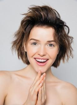 分離された灰色の壁にあなたの製品を提示する完璧な肌と歯に笑みを浮かべて興奮している若い女の子。自然の美しさは、女性を驚かせません。テキスト用の空き容量。表情豊かな表情