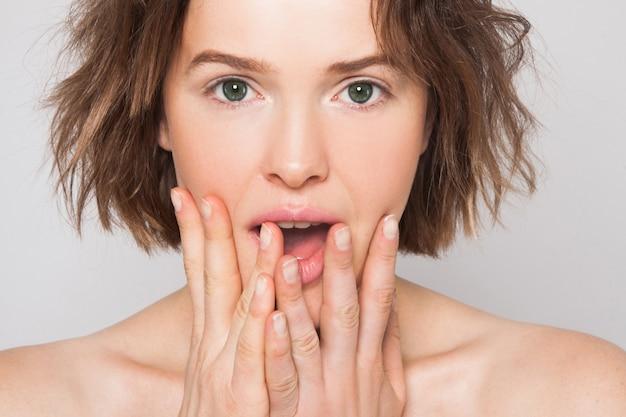 分離された灰色の壁にあなたの製品を提示する完璧な肌と歯で驚いた興奮した若い女の子。自然の美しさは、女性を驚かせません。テキスト用の空き容量。表情豊かな表情