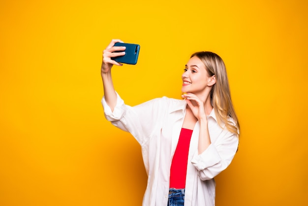 Excited young girl wearing casual clothes standing isolated over yellow wall, taking selfie with outstretched hand