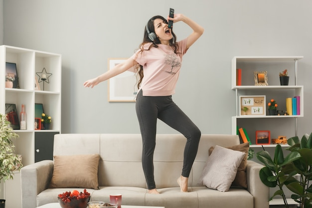 Excited young girl wearing headphones holding microphone sings standing on sofa behind coffee table in living room