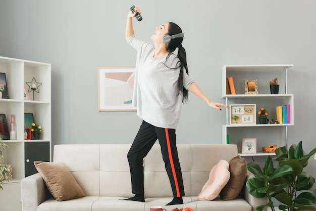 Excited young girl wearing headphones holding tv remote sings standing on sofa behind coffee table in living room