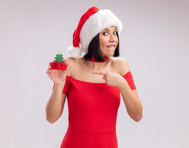 Excited young girl wearing santa hat biting lip holding and pointing at christmas tree toy with date looking at camera isolated on white background