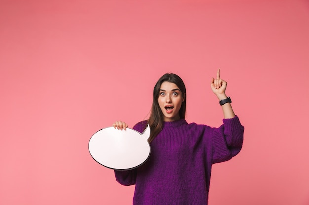 Excited young girl wearing sweater standing isolated over pink, holding empty speech bubble, pointing