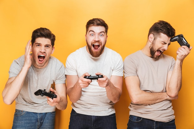 Excited young group of men friends play games with joysticks.