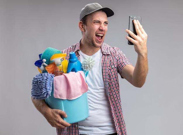 Eccitato giovane pulitore che indossa un cappello che tiene il secchio di strumenti per la pulizia parla al telefono isolato su sfondo bianco