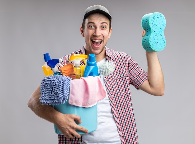 Eccitato giovane ragazzo pulitore che indossa il cappuccio tenendo il secchio con strumenti di pulizia e spugna per la pulizia isolato su sfondo bianco