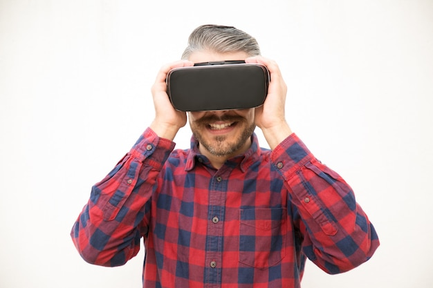 Excited young guy holding vr headset