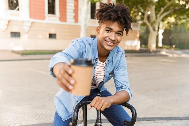 コーヒーを持って自転車で屋外を歩く興奮した若い男