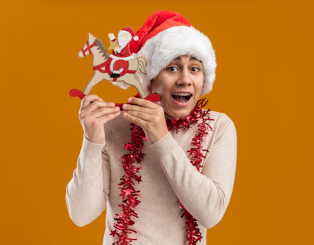 Excited young guy wearing christmas hat with garland on neck holding christmas toy isolated on yellow wall