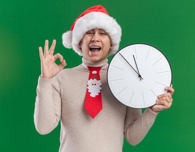 Giovane ragazzo emozionante che porta il cappello di natale con l'orologio di parete della tenuta della cravatta che mostra il gesto giusto isolato sulla parete verde