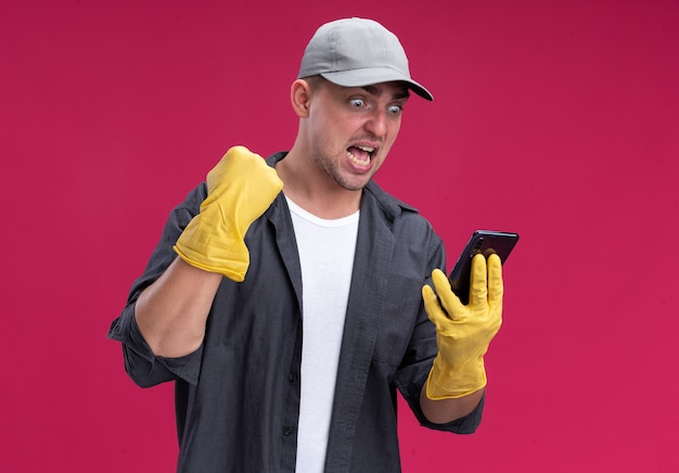 Excited young hamdsome cleaning guy wearing t-shirt and cap with gloves holding and looking at phone showing yes gesture isolated on pink wall