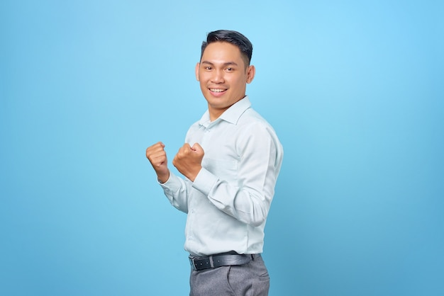 Excited young handsome businessman celebrating success with raised hand on blue background