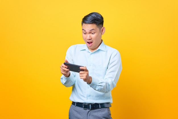 Excited young handsome businessman playing a game on mobile phone on yellow background
