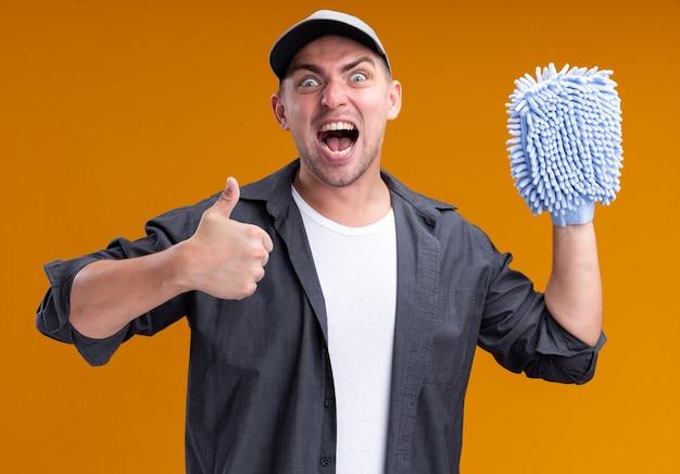Взволнованный молодой красивый уборщик в футболке и кепке держит тряпку для уборки, показывая большой палец вверх изолированно на оранжевой стене