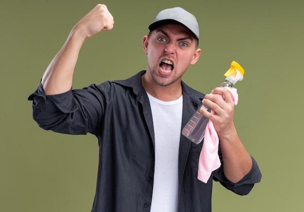 올리브 녹색 벽에 고립 예 제스처를 보여주는 스프레이 병으로 t- 셔츠와 모자를 들고 걸레를 입고 흥분된 젊은 잘 생긴 청소 남자