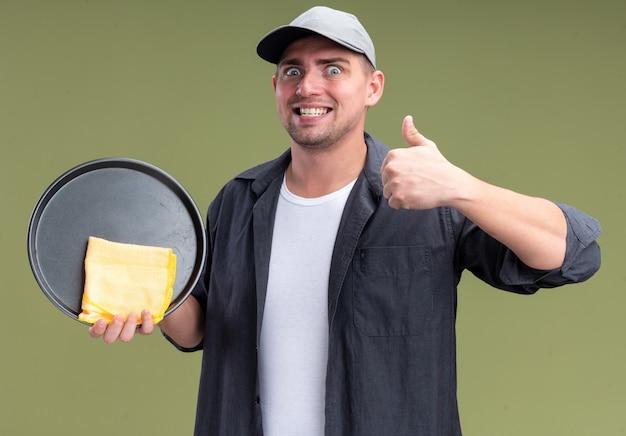オリーブグリーンの壁に分離された親指を示すトレイとぼろきれを保持しているtシャツとキャップを身に着けている興奮した若いハンサムな掃除人