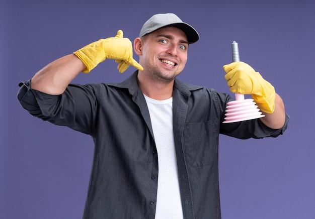보라색 벽에 고립 된 전화 제스처를 보여주는 플런저를 들고 glaves와 티셔츠와 모자를 쓰고 흥분된 젊은 잘 생긴 청소 남자