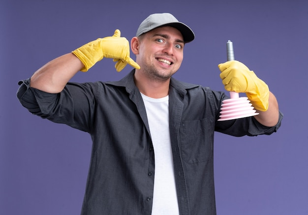 Excited young handsome cleaning guy wearing t-shirt and cap with glaves holding plunger showing phone call gesture isolated on purple wall
