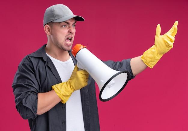 Eccitato giovane bel ragazzo delle pulizie che indossa t-shirt e berretto con guanti parla su altoparlante isolato sulla parete rosa