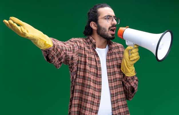 Eccitato giovane bel ragazzo delle pulizie indossando t-shirt e guanti parla sull'altoparlante diffondendo la mano isolata sulla parete verde