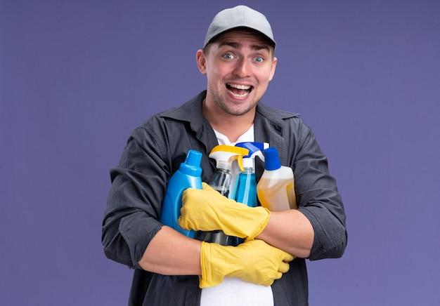 紫色の壁に分離されたクリーニングツールを保持しているキャップと手袋のtシャツを着て興奮している若いハンサムなクリーニング男