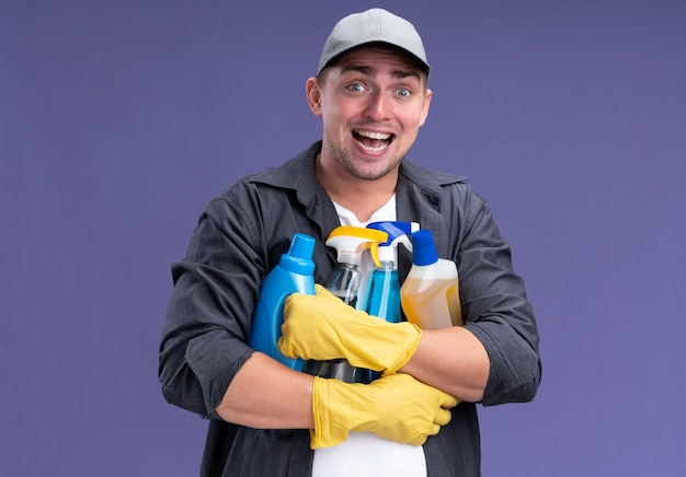 Excited young handsome cleaning guy wearing t-shirt with cap and gloves holding cleaning tools isolated on purple wall