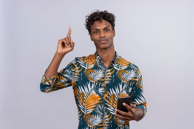 Excited young handsome dark-skinned man with curly hair in leaves printed shirt pointing upwards with his index finger while holding mobile phone